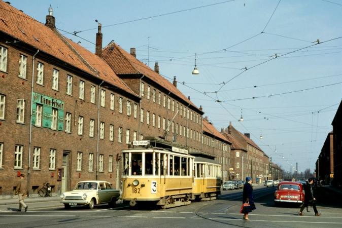 Månedens billedes første foto viser Linie 3 motorvogn med bivogn på Borgbjergsvej - på vej ind på Mozarts Plads. Markering af fodgængerovergang er foretaget - og fire fodgængere i feltet kan ses. Men endnu er der ingen lyskurve opsat i krydset.